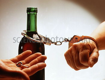 Alcohol dependence. A person handcuffed to a bottle of wine. This is an illness characterised by habitual, compulsive, long term consumption of alcohol and the development of withdrawal symptoms when drinking is suddenly stopped. Physical symptoms related to it include nausea, vomiting, abdominal pain, cramps, irregular pulse, redness and enlarged capillaries in the face. Many alcoholics require detoxification which is followed by long term treatment.